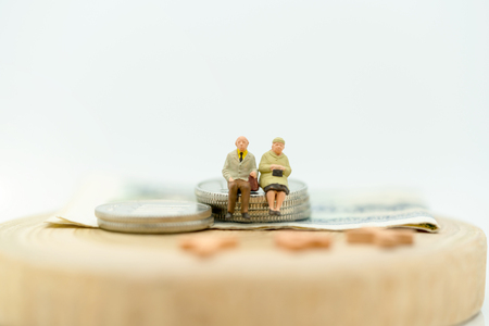 Miniature people: Happy old people standing on coins stack, retirement planning, emergency plan, life insurance and financial concept. Reklamní fotografie