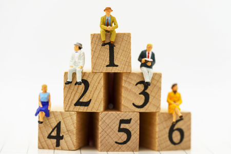 Miniature people: Business people sitting on wooden box with number 1,2,3,4,5 and 6. Business career growth, achievement, success, victory or top ranking concept. Reklamní fotografie