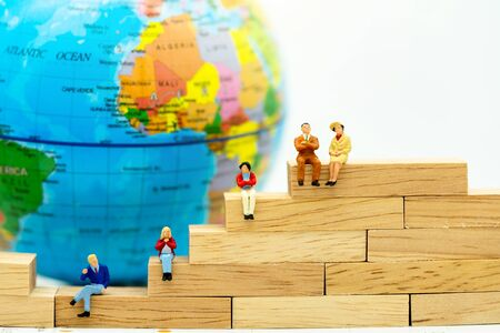 Miniature people: Business people sitting on wooden box with the world. Reklamní fotografie