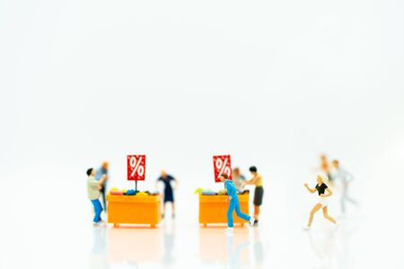 Miniature people: Shoppers buy goods on sale with discount tray. Tourism, shopping or business concept. Reklamní fotografie