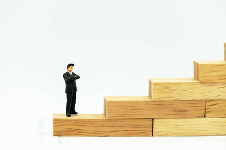 Miniature people: Business man standing on a wooden box.