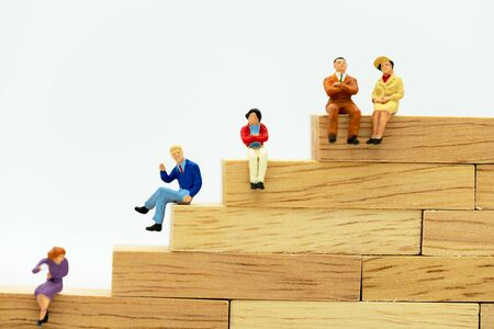 Miniature people: Business people sitting on wooden box .