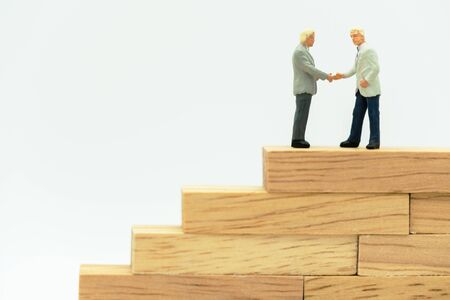 Miniature people: business handshake on a wooden box.