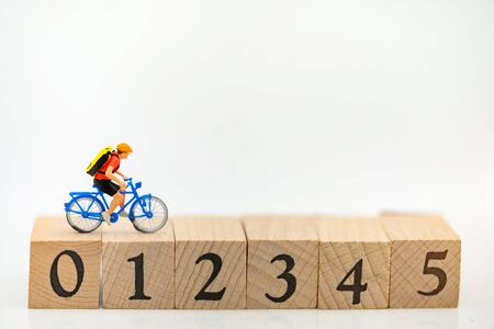 Miniature people cycling on the wooden box with number 0, 1, 2, 3, 4, 5.