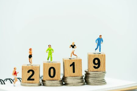 Miniature people running on a wooden box with number 2019 and coins.