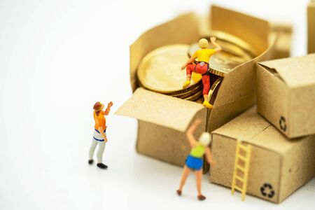 Miniature people climbing golden coins achieving top. Success, Finance, investment and growth in business concept.