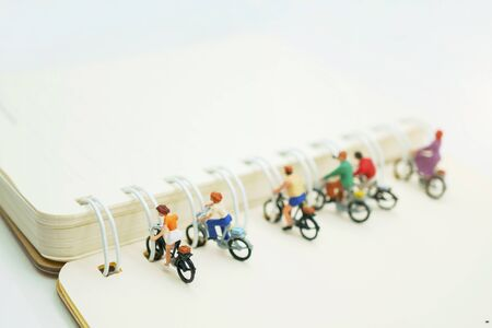 Miniature people parking on the book spine.