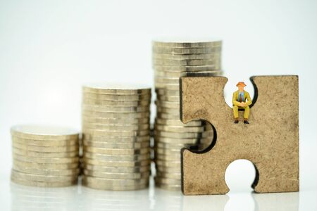 Miniature people: Businessman sitting on jigsaw puzzle and coins, Solving problems concept