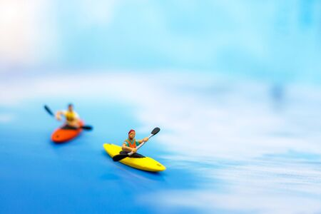 Miniature people on board of sea canoe. Summer concept. Фото со стока