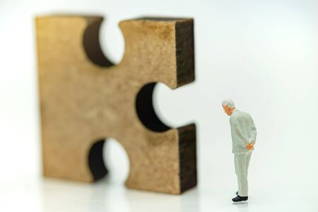 Miniature people: Businessman looking jigsaw puzzle, Solving problems concept