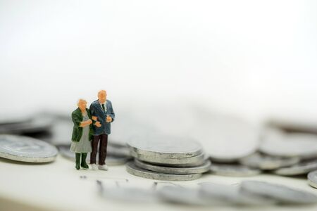 Miniaturowi ludzie: szczęśliwi starzy ludzie stojący na stosie monet, planowanie emerytalne, plan awaryjny, ubezpieczenie na życie i koncepcja finansowa. Zdjęcie Seryjne