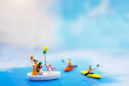 Miniature people: Family with balloon on board of sea boat. Summer concept.
