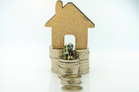 Miniature people: Happy old people standing with home, Retirement planning, Emergency plan and Life insurance Concept.