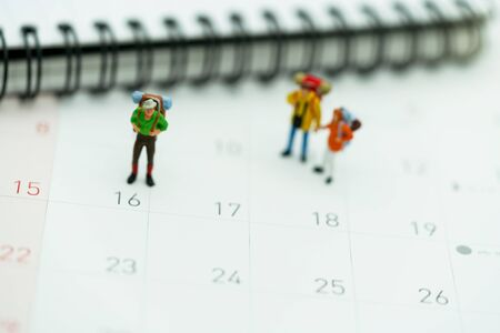 Miniature people: Tourists with backpacks standing on the travel calendar.
