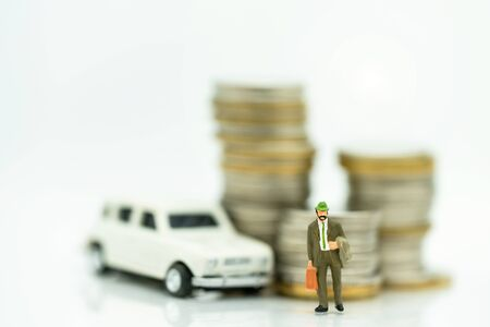 Miniature people: Businessmen standing with coins stack and car.