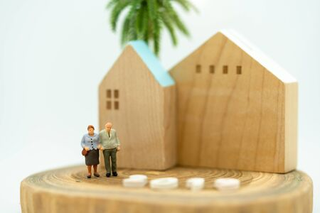 Miniature people: Happy old people standing with home, retirement planning, emergency plan and life insurance concept. Reklamní fotografie