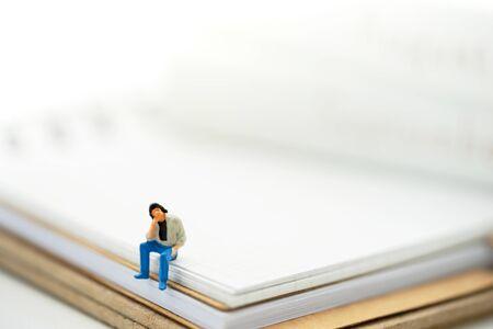 Miniature people: Businessman sitting on the book.
