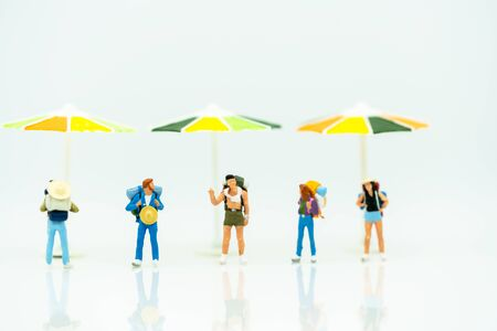 Miniature people: Tourists  with backpack standing on the beach. Summer concept.