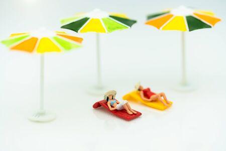 Miniature people: Tourists sunbathing on the beach. Summer concept.