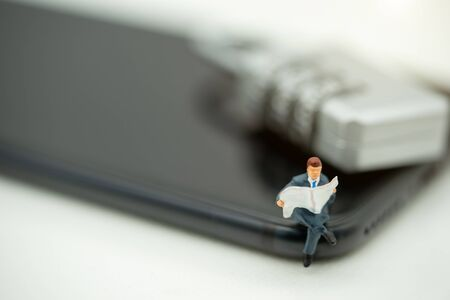 Miniature people: Business team reading book on phone with key , education or business concept. Reklamní fotografie - 132431730