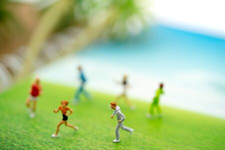 Miniature people: Tourists running on the beach. Summer Concept.