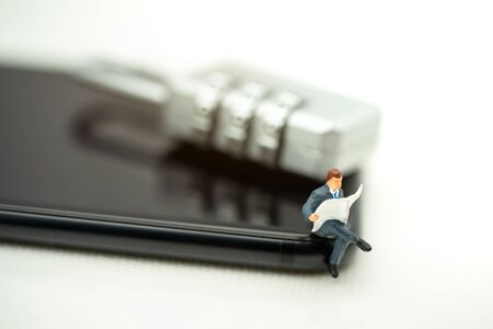 Miniature people: Business team reading book on phone with key , education or business concept. Reklamní fotografie