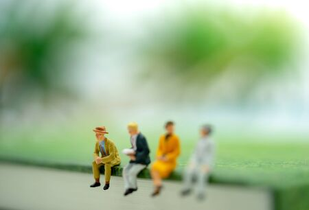 Miniature people: Businessman sitting on the book.