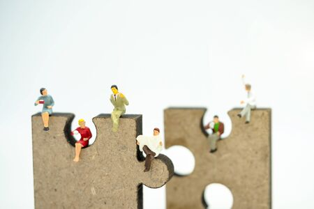 Miniature people: Business team reading book on jigsaw, education or business concept. Reklamní fotografie - 132431735