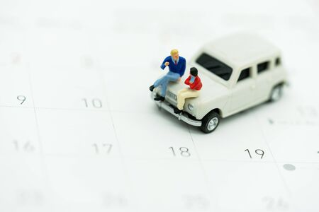 Miniature people sitting on car with calendar.