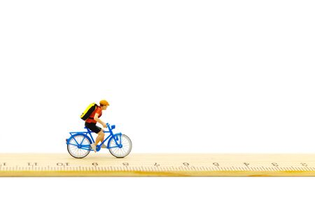 Miniature people ride bicycles on wooden ruler. Reklamní fotografie