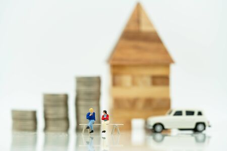 Mainature people standing with coins stack and home.  Home financial investment Concept. Reklamní fotografie