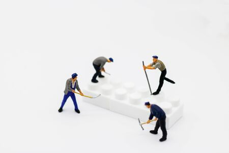 Miniature people: Worker digging white box. Service,  repair and  maintenance concept.