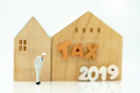 Mainature people standing with home and wording  TAX 2019.  House tax concept Reklamní fotografie