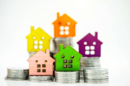 Mainature people standing with coins stack and home.  Home financial investment Concept. 免版税图像