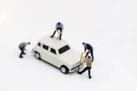 Miniature people: Workers fixing car. car service, repair, maintenance concept.