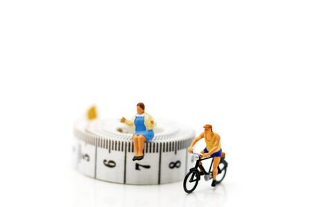 Miniature people enjoy riding a bicycle. Cycling for health Concept.
