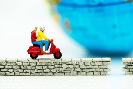 Miniature people riding bike on wall and world. Reklamní fotografie - 132431749
