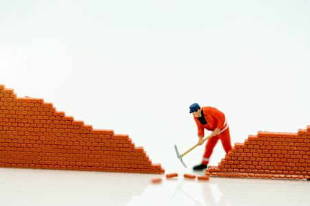 Miniature people: Worker fix the wall before the world. Concepts of finding a solution, problem solving and challenge. Reklamní fotografie - 132431751