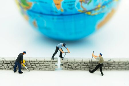 Miniature people: Worker fix the wall before the world. Concepts of finding a solution, problem solving and challenge. Reklamní fotografie - 132431750