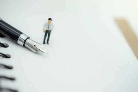 miniature people standing with fountain pen on paper with white background.