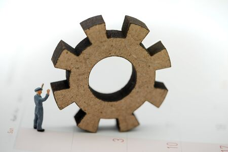 Miniature people with gear cog symbol on calendar, Business management and working process concept. Reklamní fotografie - 132431758