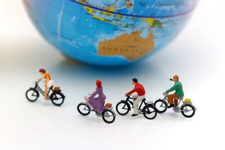 Miniature people enjoy riding a bicycle with globe.