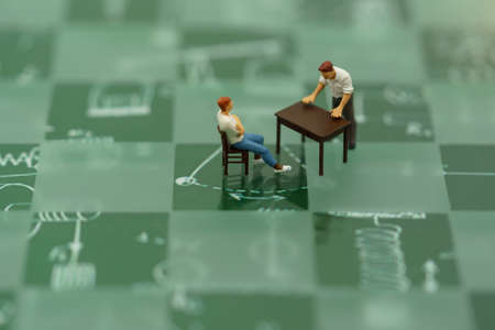 Miniature people sitting with table on Green chess board.