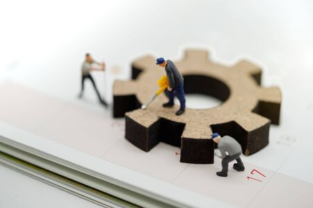 Miniature people with gear cog symbol on calendar, Business management and working process concept. Reklamní fotografie - 133559425