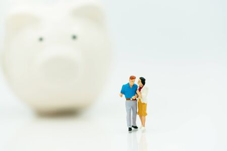 Miniature people: Couple standing with piggy bank.