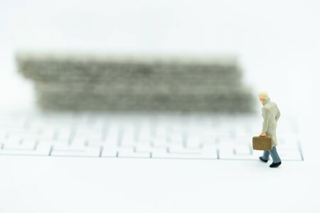 Miniature people: Businessman walking to wall in maze. Concepts of finding a solution, problem solving and challenge.
