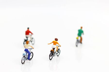 Miniature people enjoy riding a bicycle on white background. Reklamní fotografie