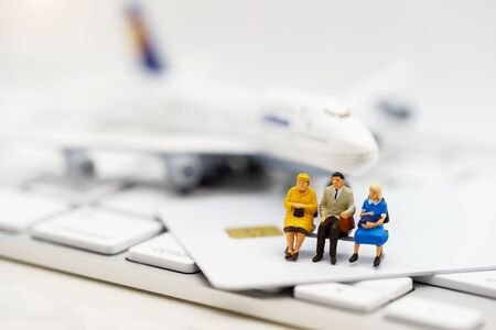 Miniature people sitting on credit card with keyboard and airplane. Reklamní fotografie - 133559670