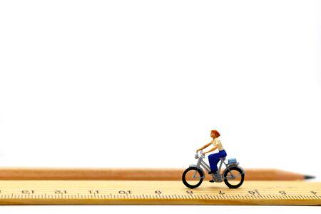 Le persone in miniatura vanno in bicicletta su un righello di legno.