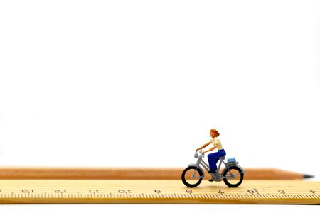 Miniature people ride bicycles on wooden ruler. Imagens